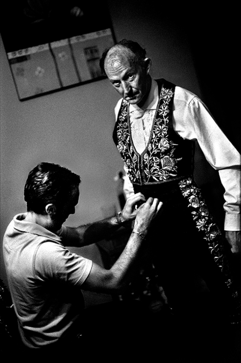 A bullfighter is getting dressed.