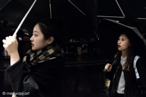 Central London, Two ladies during a rainy night sheltering under their umbrella