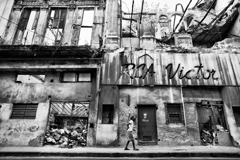 A Women walks past what is left of the RCA Victor Building in Central Havana