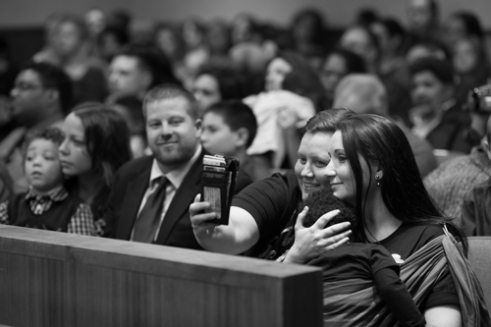 """Danielle Sharkey (left) and Ali Beck (right) take a """"selfie"""" with their daughter Kendrik Sharkey during the Adoption Day ceremony at the Monroe County Courthouse in Rochester, N.Y. on Nov. 20, 2015. Over a dozen families all adopted children at the courthouse for Monroe County's annual Adoption Day. There are over 450 children currently in foster care in Monroe County, out of over 400,000 in the nation."""