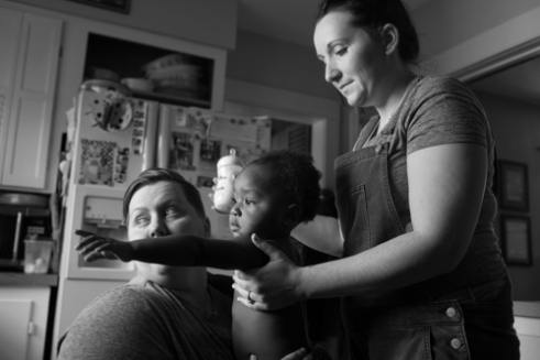 Dani and Ali lift up their daughter, Kendrik, at their home in Rochester, N.Y. on Nov. 25, 2015. Dani and Ali had been foster parents for Kendrik for over a year, picking her up from the hospital six days after she was born.