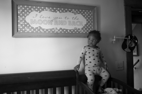 """Kendrik Sharkey gets ready for a nap in her crib at her home in Rochester, N.Y. on Nov. 25, 2015. """"I just adopted the cutest kid on the planet, who makes my day every day, and that's what makes it worth it,"""" Dani said."""