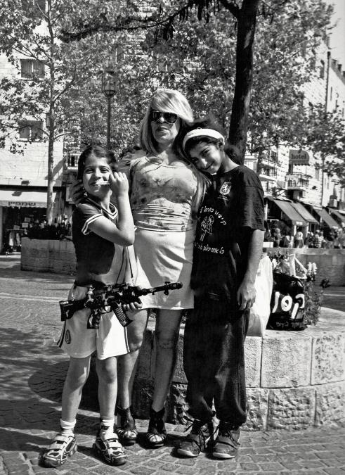 Tel Aviv, Israel 2010, modern Jewish mum with kids carrying fake guns.