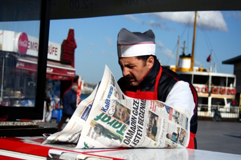 Street vendor reading newspaper Istanbul.