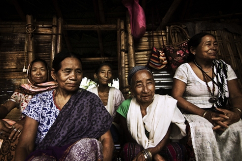 Women sitting inside an under-construction house in Khonsa Village, Tirap District. Men and Women from all households gather for the construction of any house in their locality. It usually takes 3 days to build a house. The women prepare the food that involves pork-meat and rice beer, known by the name of Kham in their local language.