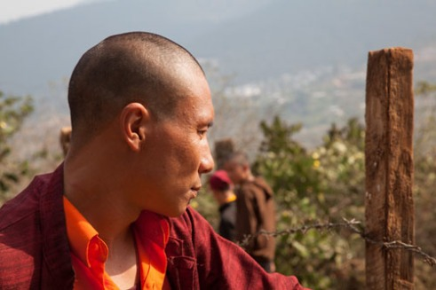 A monk looks over his charges as they plant agricultural crops for the summer.