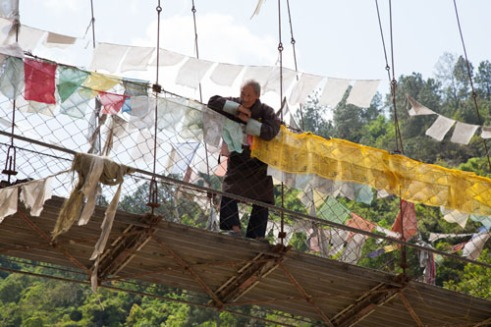 Swing bridges over the rivers of Bhutan are common often decorated with prayer flags. This older man dressed in traditional male outfit was overlooking the tourists loading them selves into river rafting boats to raft down the rapids of the river.