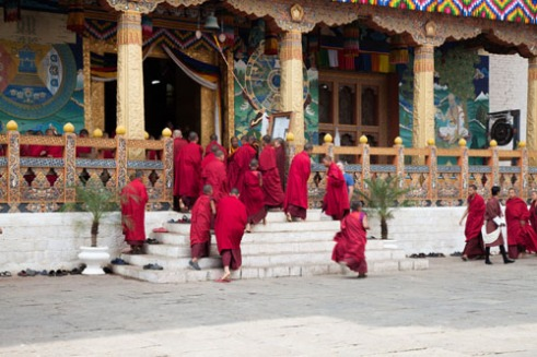 Young monks dressed in traditional ruby red robes rush at the last minute to make prayers. At the time they were practicing for the Rhododendron festival that took place two days later. This Punakha Dzong monastery sits on the confluence of the Pho Chhu (father) and Mo Chhu (mother) rivers in the Punakha–Wangdue valley.