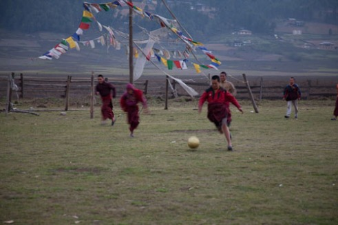 Young monks play football using goals covered in Prayer Flags. While the monks spend significant time in religious studies and prayers, these grasped the opportunity to rush out and play a quick game of football. All of these monks were orphans and belong to a remote monastery where the abbot at the time was only 30 years old relying on donations to maintain the operations of the monastery in Bumthang and to provide food and clothing for the boys.