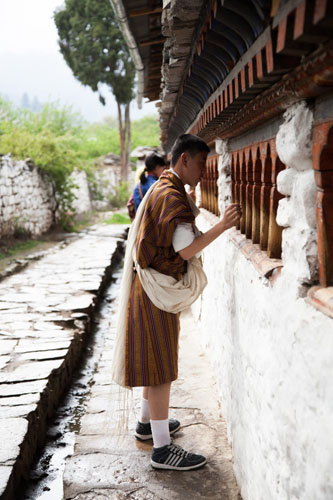 Spinning prayer wheels. This is normally done clock wise as is circumnavigating the monastery and shrines. In this instance this teenage boy spun multiple wheels progressing slowly round the outside of the monastery.