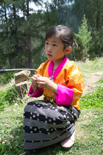 Young girl dressed in traditional but festival wear. She was weaving flowers while her parents and her uncle, a monk, were preparing food for a picnic. We were invited to join for tea and food as we were hiking past.
