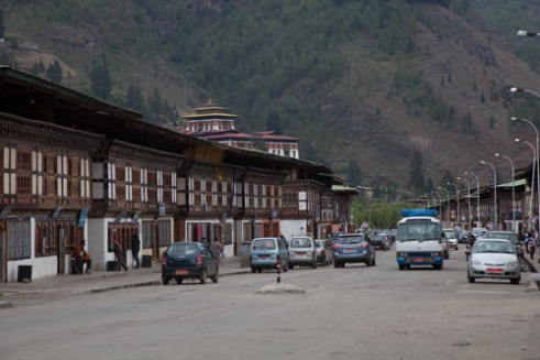 Main road of Paro with traditional architecture that now houses traditional shops next to modern shops. There is a strong influence of both Chinese and Indian cultures, including goods in the shops, as there are the direct economical strong neighbours that cover most of the borders of Bhutan, leaving the country squeezed from both sides.