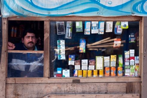North Zone of The Jungle, Calais, France, March 2016 In order to survive in the Jungle men has set up various kinds of trade. Groceries, hairdressers, coffee shops, restaurants are found there. These refugees initiative gave rise to a black economy within the Jungle. Sikandar Zamaan is Pakistani. He runs his grocery where calling cards, packets of tobacco for 2 Euros, and a wide range of soda are for sell.