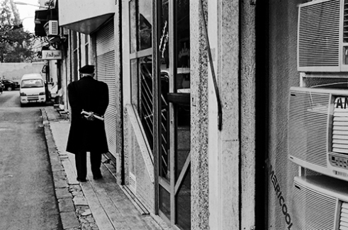 An old man walks at lunchtime, where this commercial street is full of life at other times. 2010-01-15