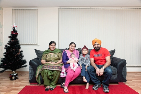 Gurinder and Harpreet with family Sikh communities in Scotland have a long history, stretching back to the 19th century when the first families arrived from India. Scottish Sikhs have their own tartan and are often to be found wearing kilts on special occasions. This portrait shows a family who represent a more recent arrival to Scotland. Gurinder and his wife Harpreet came to Scotland from New Delhi with their son Brahmjot. Their daughter Siaana was born in Edinburgh; I was also lucky to meet Gurinder's mother Balbir who comes to Scotland every few months to visit and help her son and his wife with the family. Their religion is an intrinsic part of their own lives while also playing an important role in the wider community. Although traditional, they have also adopted some local customs, this Christmas tree for example. Edinburgh, Scotland, 2012