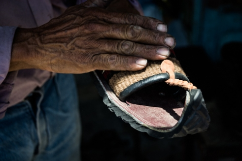 A shoemaker shows the product to tourists, the main source of profit in this area. DOUZ