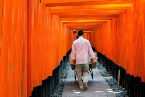 A man walks through Fushimi Inari shrine with a wheelbarrow Kyoto