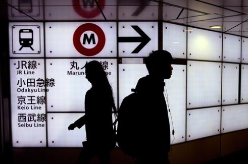 Tokyo Metro passengers make their way through the crowds to catch their train at the Shinjuku-Sanchome station. Tokyo