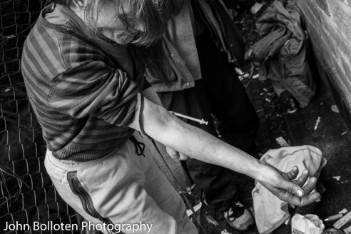 A heroin-addicted homeless woman takes off the tourniquet with the needle still in her arm in a public injecting site in Bradford. The floor is littered with needles, syringes and other injecting paraphernalia.