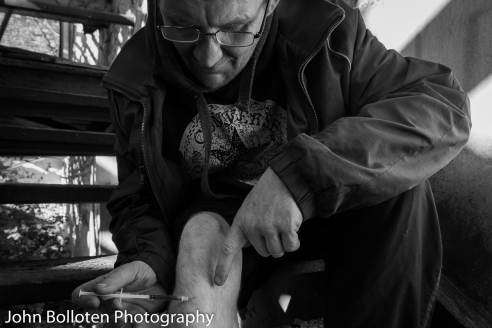 A long-term heroin user injects a speedball into his leg. A speedball is heroin and crack in the same syringe.