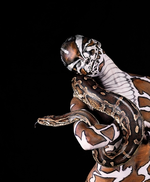 Burmese Python being held by woman painted with the python's markings.