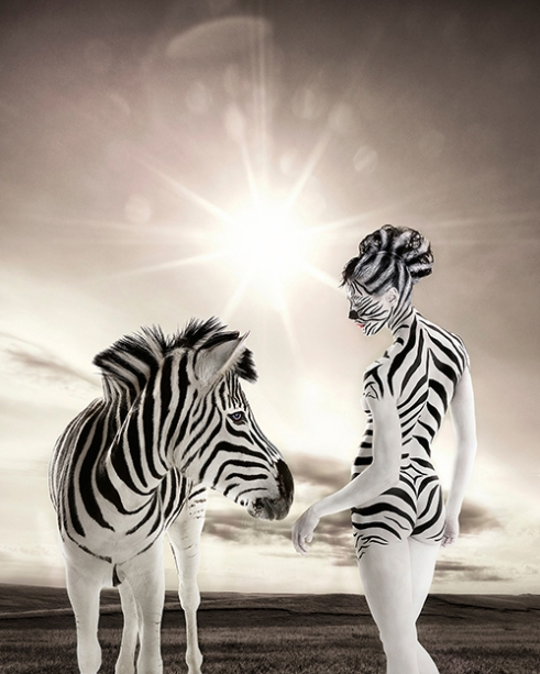 Zebra and female human interacting with plains in the background.