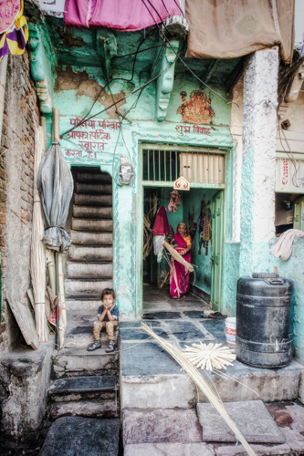 Udaipur,Rajasthan, India. While his mother carries out her whicker for weaving, her son sits on the stone steps, alone, looking a little bored.