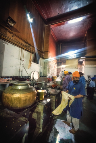 Old Delhi, India. Gurudwara Bangla Sahib. Men and women of the Sikh faith work together to feed thousands visitors to the temple who eat there for free. Both the giving and receiving of food is considered sacred.