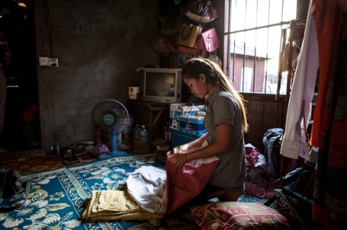 """Bann, garment worker. Bann is a 27 year old garment worker.she lives in a 2.5 x2m rented room with her husband. Mann has worked at the nearby factory and lived in this room for just over 12 months. Most of the 500m walk from the main road to her house is unlit. 'I feel unfordable when I leave work. I often run one at night as these is a lot of verbal harassment when you leave the factor. men call out to you' he girl, where you going?"""" sometimes they follow you for a laugh. This is scary. The last 100m is pitch black and I run'' Phnom Penh, Cambodia"""