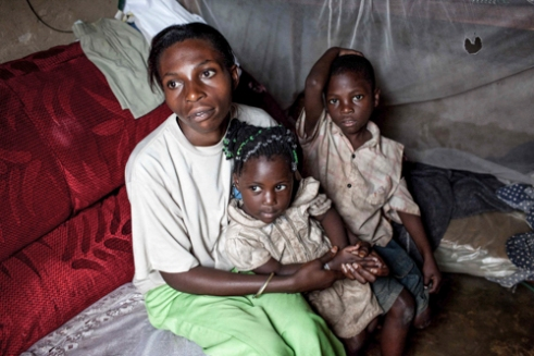 Hajara Mukyala's with two children of her children. Hajara is a sex worker and violence survivor. She was raped when she was 14 and became pregnant and was infected by HIV from the rape. She had no choice but turn to prostitution to give her children an education. Hajara suffered horrific violence from her customers. She joined Tusitukirewamu Women's Group in Bwaise to help other women.