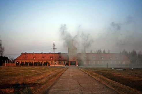 """Coal smoke billows from the former SS Headquarters at Auschwitz II - Birkenau, which is now an active Catholic Church for the village of Brzezinka . The large cross above the building is prominent in the skyline of the camp and has been protested by many Jewish organizations as an effort to """"Christianize"""" the Holocaust."""