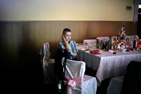 A young boy at a wedding reception above the firehouse in the village of Brzezinka (Birkenau).