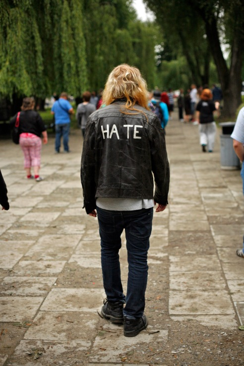 A tourist at Auschwitz wearing a jacket with a punk-rock reference.