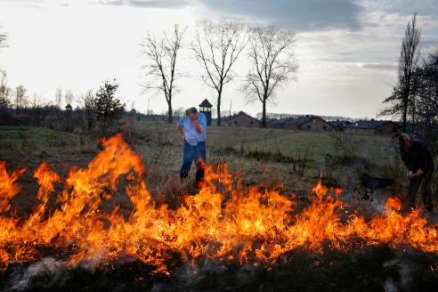 A controlled burn of a crop field in the Polish town of Brzezinka, in view of the extermination camp Auschwitz II - Birkenau.