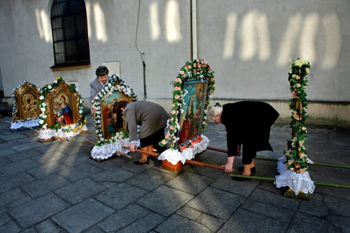 Women prepare for an Easter procession around an old church in the Oswiecim town square. The church is across the street from the restored Jewish Synagogue and education center