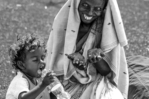 Mother and Child Living with the effects of Leprosy, a mother begs for money while her child plays. Chennai, India