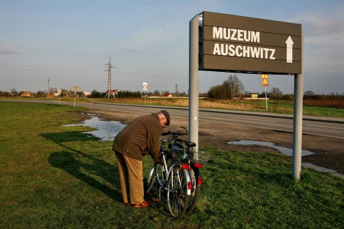 An elderly man from Oswiecim locks his bike to a sign at Auschwitz II - Birkenau directing visitors to the Auschwitz I museum site.