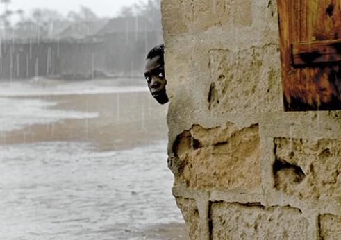 TANZANIA Rain This was taken in Tanzania. I was working with WaterAid shooting stories about water and sanitation. We arrive at a village that was about to sign an agreement that would start the process to get help. The chief and all the village were crammed into this building but something was wrong and the chief would not sign. So as not to influence the situation I and my WA contact went and sat in the car. That's when the skies let rip. As with most of the places we went to westerners were a rare sight so the children were curious. This was a fleeting second but it was ours. No agreement was reached that day. I really hope it has since.