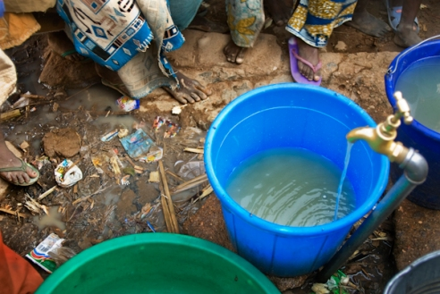 Water from a water-well which is located less than a hundred yards from the nearby open dump site runs into a bucket. Well-water like this is found in many neighborhoods of Kano and is used by residents for washing dishes, clothes and bathing. Kano, Nigeria