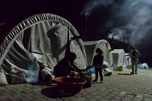 After Dinner They are lodged in a single-room tent. They no longer have a kitchen or a dishwasher. After dinner they do the dishes in front of the tent. These are the last tasks of the day at a refugee camp. A little girl keeps her mother company as she does the dishes. Besiri Refugee Camp, 05.Dec.2014