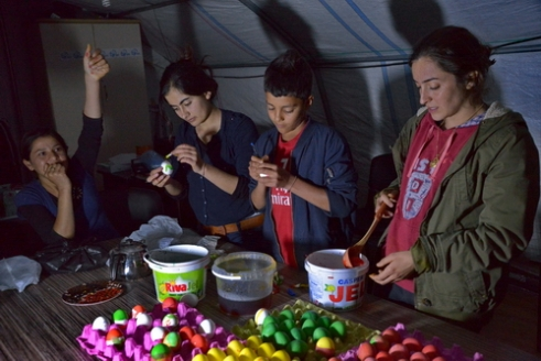 """Celebrating Red Wednesday"" A day earlier they paint boiled eggs to different colors. Eggs symbolize World. Feast day everyone bump the egg in the hands of someone else's eggs. Many aspects it is similar of the Christian Easter feast. They are painting eggs for the feast even though in a refugee camp under a tent. Place: Sirnak Refugee Camp, 14.April.2015"