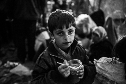 The boy is eating hot soup which he got from volunteer.