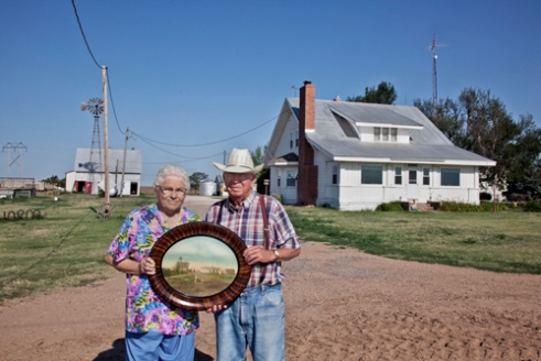 Laurence and Pauline Schwarm with a 1912 photograph his father's original farmstead, south of Greensburg.