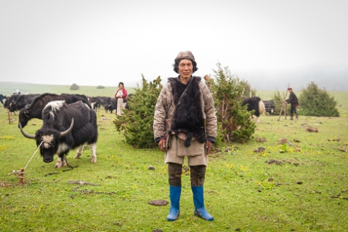 A herder wearing a jerkin made of yak hide for extra warmth.