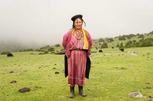 A Brokpa women in tradition clothes made from Yak hair and sheep's wool. Their distinctive hat known as 'tsipee cham' is made of yak felt with long twisted tufts, said to prevent the rain from running into their faces.
