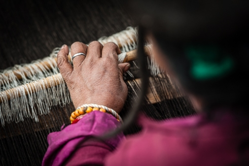 Sonam carefully weaves the yak yarn into a blanket for the winter months.