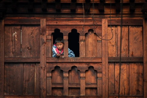 21st Century problem. A young Brokpa boy hangs out of the window for better mobile phone reception.