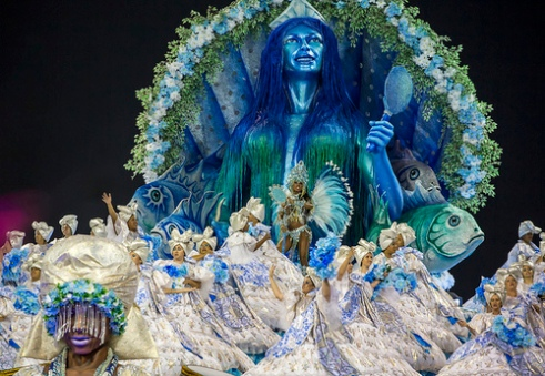 São Paulo, Brazil- February 7, 2016: Brazilian samba dancers performing on a float in costume for the samba school Academicos do Tucuruvi at the Amhembi Sambadrome in Sao Paulo. The float represents the African god Yemanja, the queen of the sea. Her mythological significance is tied to the African diaspora created when slaves were brought across the sea to Brazil.