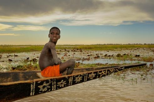 Little Fulani boy in handmade canoe. Near Djenne