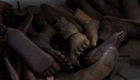 Wooden feet used as prosthetics, for landmine victims, sit in a pile on a workshop floor at a small hospital complex in Tchemulane, Mozambique. Long forgotten landmines from past conflicts claim many lives and limbs each year. (2005)